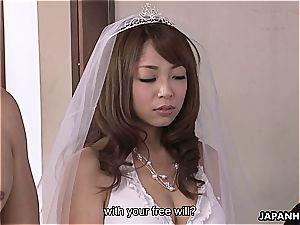 asian bride sucking wood during her wedding